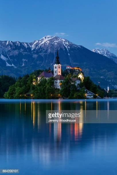 church tower and mountains reflecting in still lake - eslovenia fotografías e imágenes de stock
