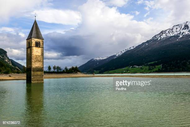 church under water, drowned village, mountains landscape and peaks in background. reschensee lake reschen lago di resia. italy, europe, südtirol, south tyrol, upper adige, alto adige - tower stock pictures, royalty-free photos & images