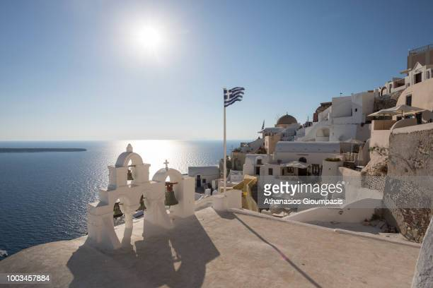 Church with Bell Tower and greek flag at Oia caldera with views to the sea caldera and volcano on July 16 2018 in Santorini Greece