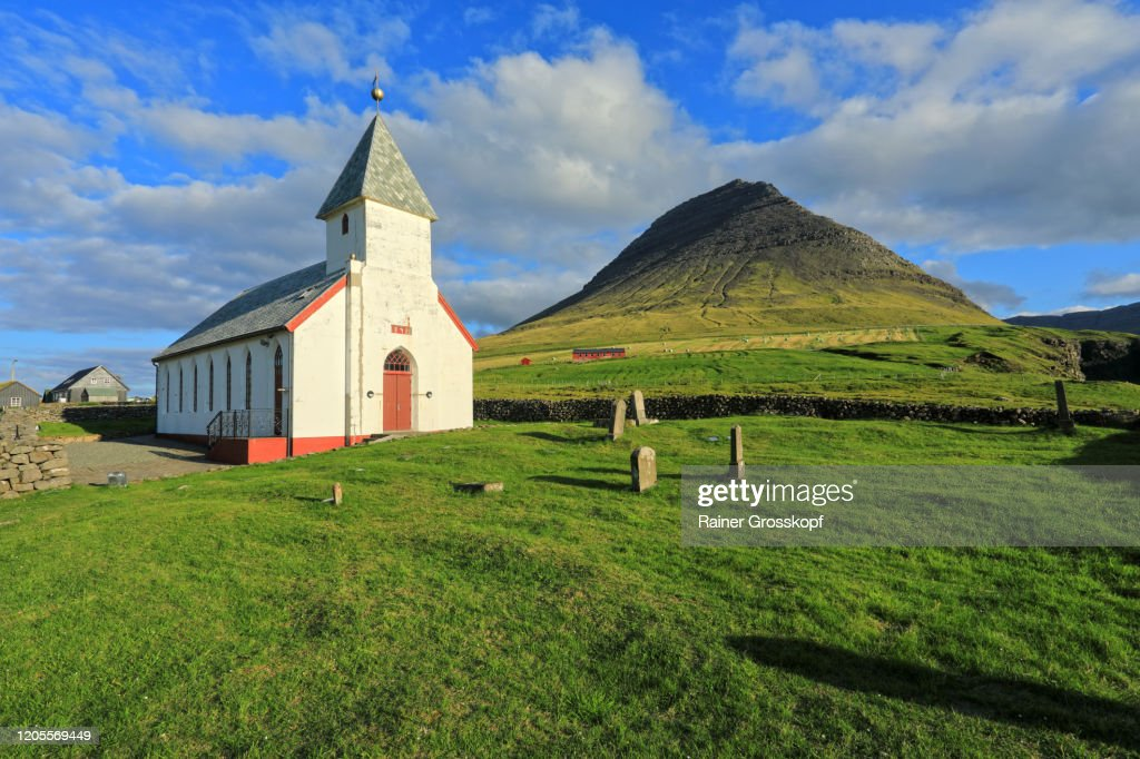 A church with cemetery on a meadow wit a pyramidal mountain is in the background : Stock-Foto