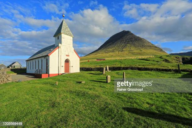 a church with cemetery on a meadow wit a pyramidal mountain is in the background - rainer grosskopf stock-fotos und bilder
