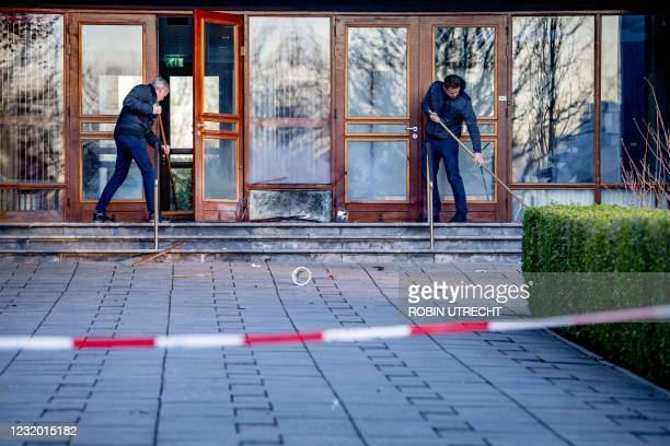 Church workers clean up the damages outside the Mieraskerk , following a small explosion, on March 30, 2021. - Dutch police said a small explosion on...