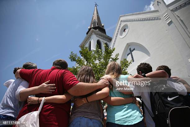 A church youth group from Dothan Alabama prays in front of the Emanuel AME Church on the onemonth anniversary of the mass shooting on July 17 2015 in...