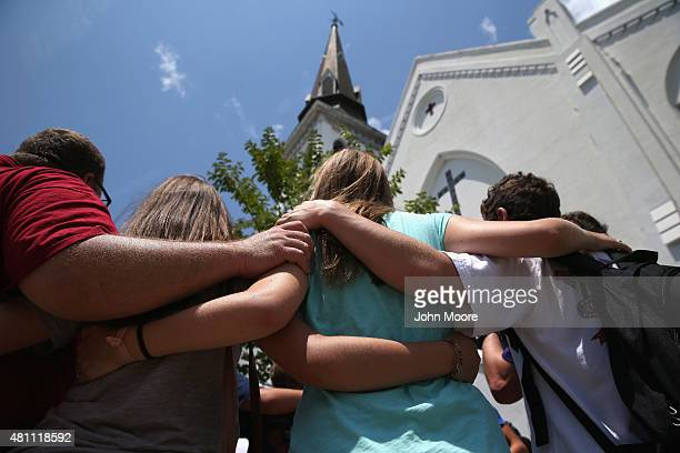 A church youth group from Douthan Alabama prays in front of the Emanuel AME Church on the onemonth anniversary of the mass shooting on July 17 2015...