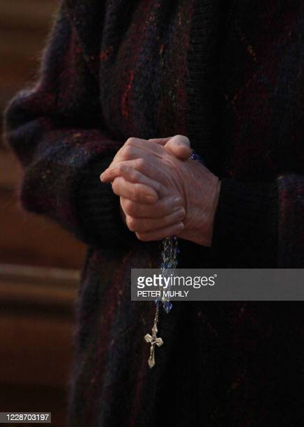 Churchgoer holds a cross and rosary beads as the head of the Catholic Church in Ireland, Cardinal Sean Brady, speaks in Saint-Patricks Cathedral on...