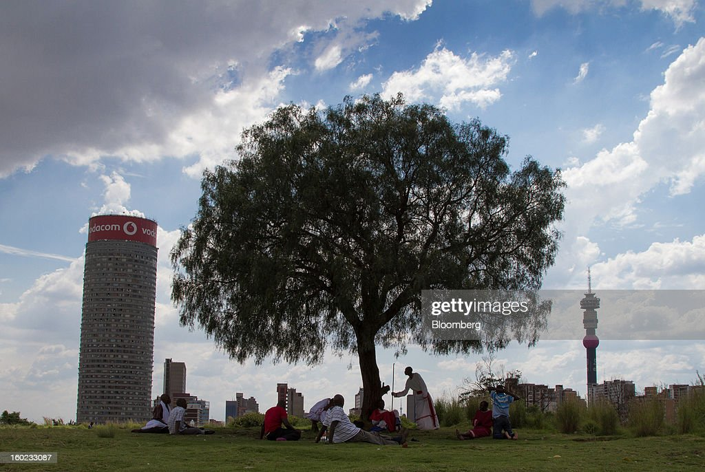 Church-goers pray during a service with a pastor on a hill overlooking the Vodacom Group Ltd.-branded Ponte tower in Johannesburg, South Africa, on Monday, January 28, 2013. Almost two decades after Vodafone Group Plc entered Africa, the region -- where most people earn less than $2 a day and mobile phone towers run on diesel -- is turning into one of the company's biggest profit generators. Photographer: Nadine Hutton/Bloomberg via Getty Images