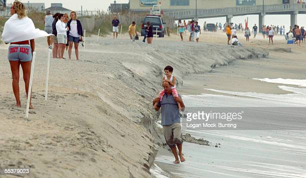 Churchill and Vivian Hornstein walk on the low side of a berm formed by waves from Hurricane Ophelia on September 11 2005 in Wrightsville Beach North...