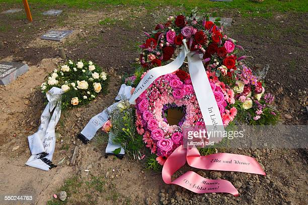 churchyard death mourning entombment grave urn tomb flowers roses wreath coronal floral arrangement ribbons