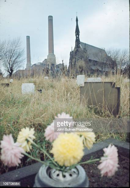A churchyard in Manchester with factory chimneys rising behind it England 1976