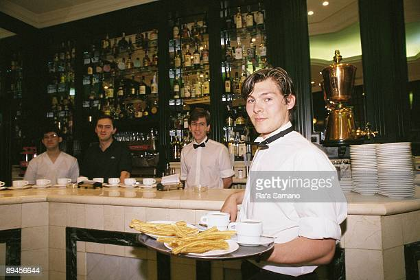 Churreria San Gines Madrid Waiter with a plate with 'churros' typical Spanish food and chocolate cups