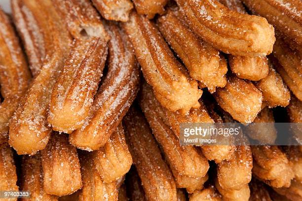 churro pastries on display in market - churro stock photos and pictures