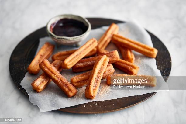 churros and chocolate dipping - churro stock photos and pictures