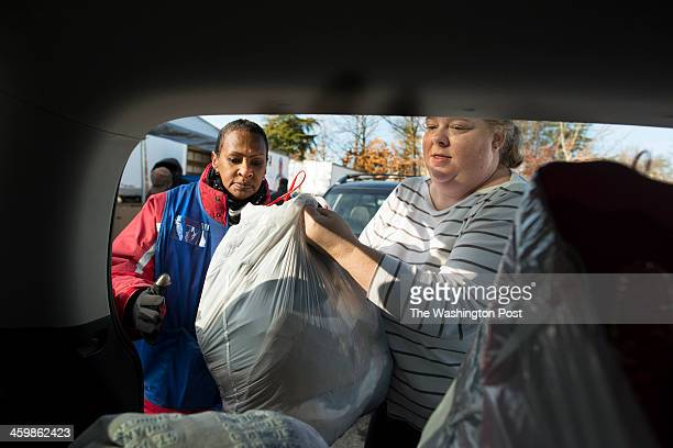 Chyerl Woodard heps Leigh Warren unload her donations at the Goodwill donation dropoff center in Arlington VA on December 31 2013 As the year ends...