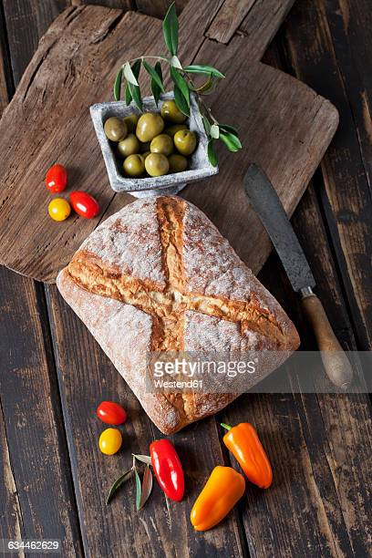 Ciabatta bread with green olives in bowl, tomatoes and mini capsicum on wood