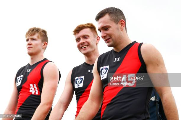 Cian McBride, Ross McQuillan and Conor McKenna of the Bombers walk off after competing in the VFL curtain-raiser match before the Marsh Community Cup...