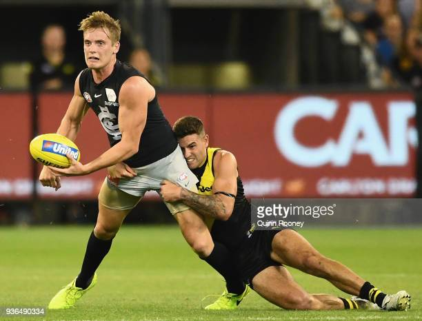 Ciaran Byrne of the Blues handballs whilst being tackled by Jack Graham of the Tigers during the round one AFL match between the Richmond Tigers and...