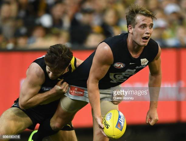 Ciaran Byrne of the Blues handballs whilst being tackled by Reece Conca of the Tigers during the round one AFL match between the Richmond Tigers and...