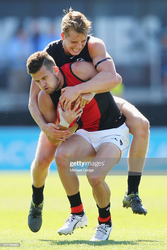 Ciaran Byrne of the Blues tackles Jackson Merrett of the Bombers during the 2016 AFL NAB Challenge match between Carlton and Essendon at Ikon Park on February 28, 2016 in Melbourne, Australia.