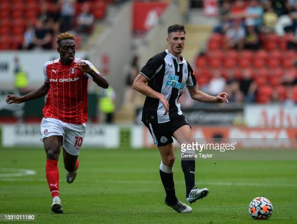 Ciaran Clark of Newcastle United FC passes the ball after being pursued by Olayinka Ladapo of Rotherham United during the Pre Season Friendly between...