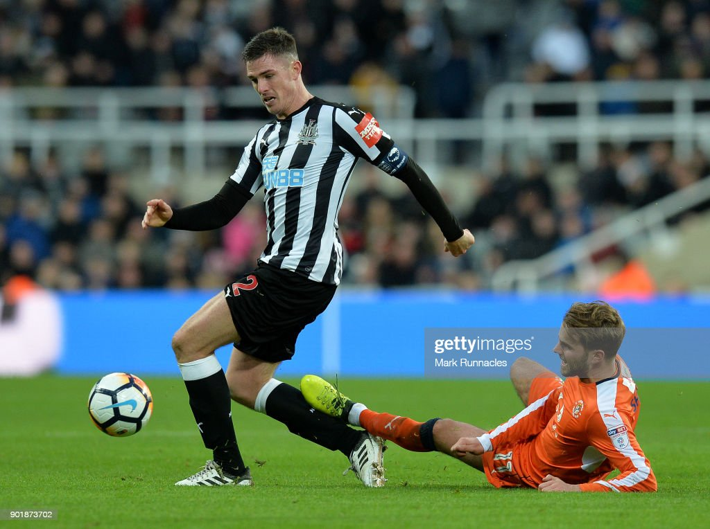 Ciaran Clark of Newcastle United is tackled by Andrew Shinnie of Luton Town during the Emirates FA Cup Third Round match between Newcastle United and Luton Town at St James' Park on January 6, 2018 in Newcastle upon Tyne, England.