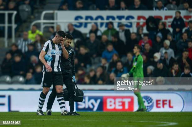 Ciaran Clark of Newcastle United walks off the pitch with a head injury accompanied by Newcastle's Physiotherapist Michael Harding during the Sky Bet...
