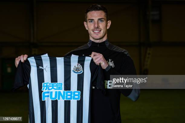 Ciaran Clark poses for a photograph holding a club home kit after signing a new contract at the Newcastle United Training Centre on January 20, 2021...