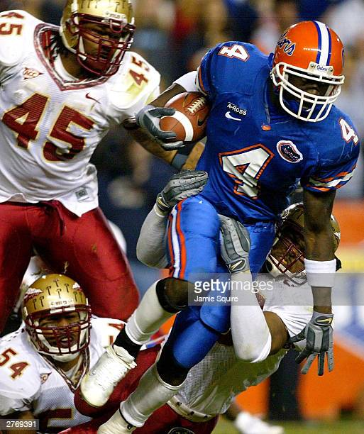 Ciatrick Fason of the Florida Gators carries the ball as Michael Boulware Darnell Dockett and AJ Nicholson of the Florida State Seminoles pull him...