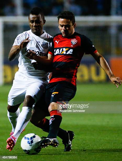 Cicinho of Santos and Juan of Vitoria in action during the match between Santos and Vitoria for the Brazilian Series A 2014 at Pacaembu stadium on...