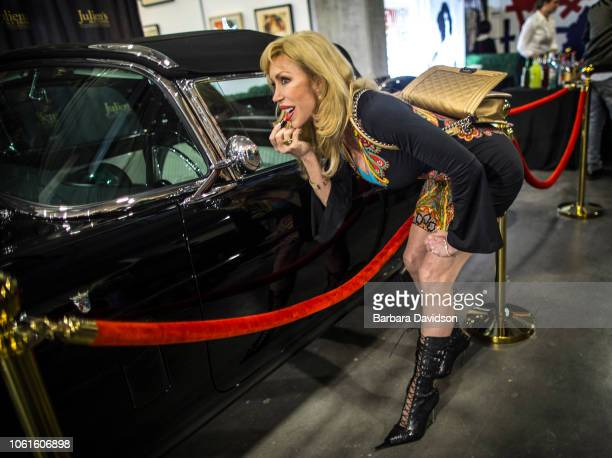 Cie Allman Scott puts on her lipstick in the side mirror of Marilyn Monroe's 1956 black Thunderbird for purchase at Julien's Auctions 'Street...