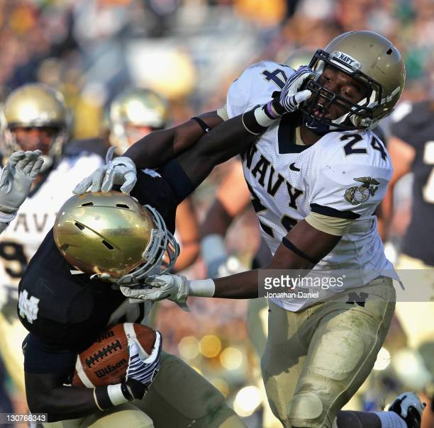 Cierre Wood of the Notre Dame Fighting Irish and Parrish Gaines of the Navy Midshipmen grab each other by the face mask at Notre Dame Stadium on...