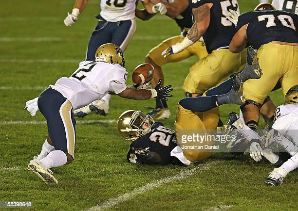 Cierre Wood of the Notre Dame Fighting Irish fumbles the ball at the goal line in overtime as Lafayette Pitts of the Pittsburgh Panthers moves to...