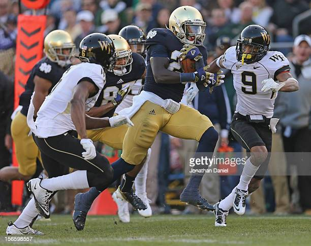 Cierre Wood of the Notre Dame Fighting Irish is chased by Kevin Johnson and Chibuikem Okoro of the Wake Forest Demon Deacons at Notre Dame Stadium on...