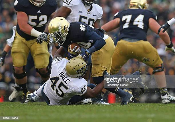 Cierre Wood of the Notre Dame Fighting Irish is dropped for a loss by Shayne Hale of the Pittsburgh Panthers at Notre Dame Stadium on November 3 2012...