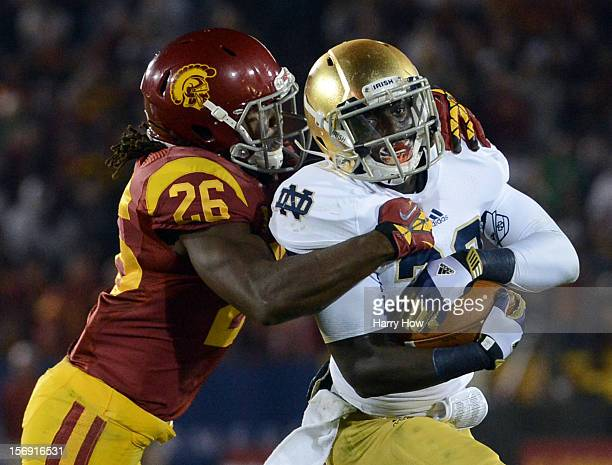 Cierre Wood of the Notre Dame Fighting Irish protects the ball as he is tackled by Josh Shaw of the USC Trojans during a 2213 Notre Dame win at Los...