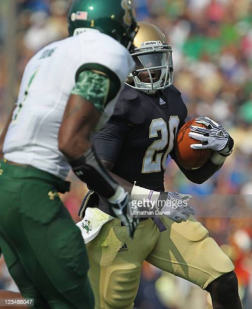 Cierre Wood of the Notre Dame Fighting Irish runs and watches as Jerrell Young of the University of South Florida Bulls pursues at Notre Dame Stadium...