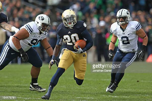 Cierre Wood of the Notre Dame Fighting Irish runs past Rodney Fuga and Spencer Hadley of the BYU Courgars at Notre Dame Stadium on October 20 2012 in...