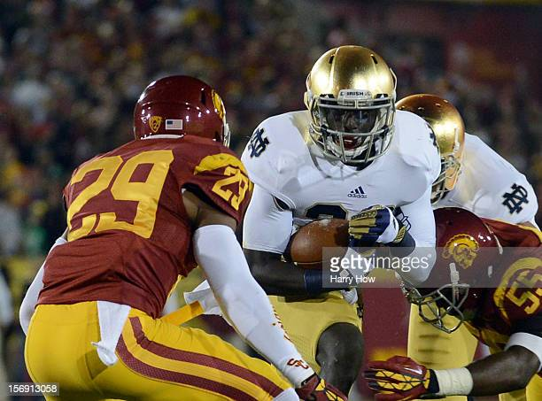 Cierre Wood of the Notre Dame Fighting Irish runs with the ball as he is tackled by Jawanza Starling and Lamar Dawson of the USC Trojans at Los...