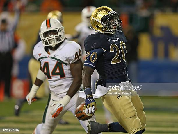 Cierre Wood of the Notre Dame Fighting Irish scores a touchdown past Eddie Johnson of the Miami Hurricanes at Soldier Field on October 6 2012 in...