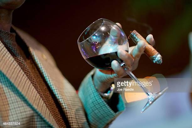 Cigar aficionado enjoys a glass or wine with a cigar during the opening gala night of the week-long International Habano Cigar Festival on February...