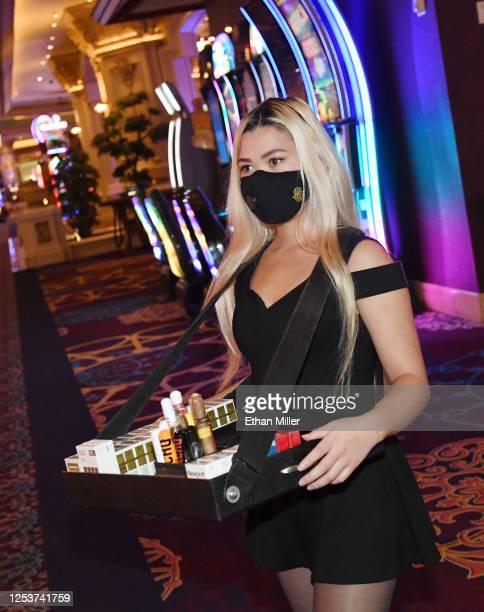 Cigar hostess Ayeesha Fabella wears a mask on the gaming floor at Mandalay Bay Resort and Casino after the Las Vegas Strip property opened for the...