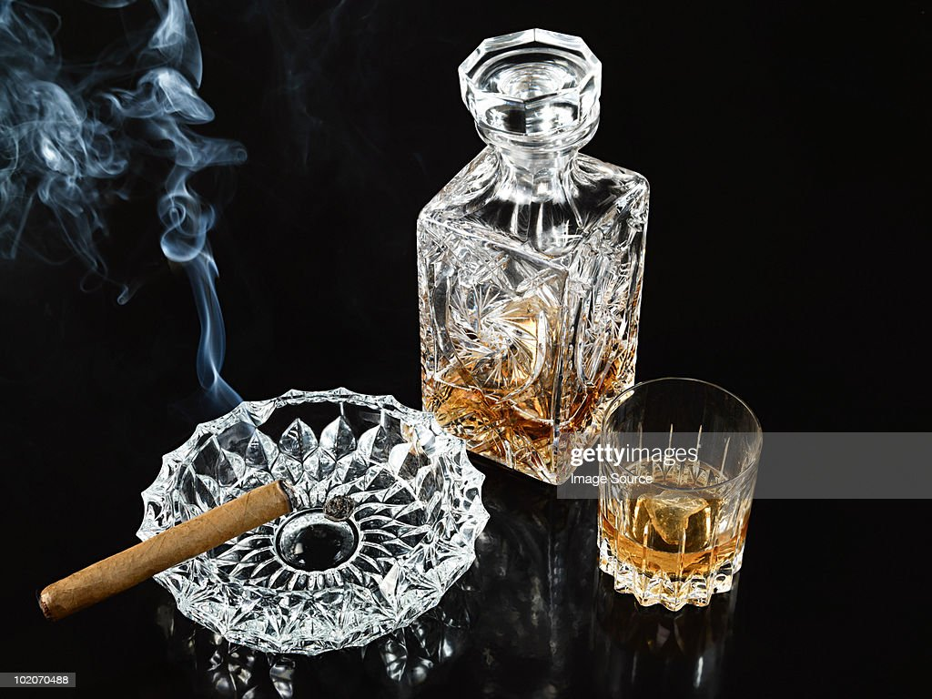 Cigar in ashtray with decanter and tumbler of whiskey : Stock Photo