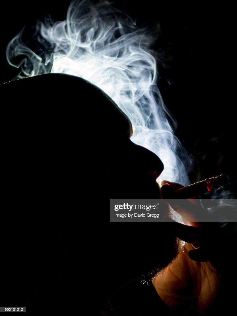 Cigar Smoke Dances in the Light 3 : Stock Photo