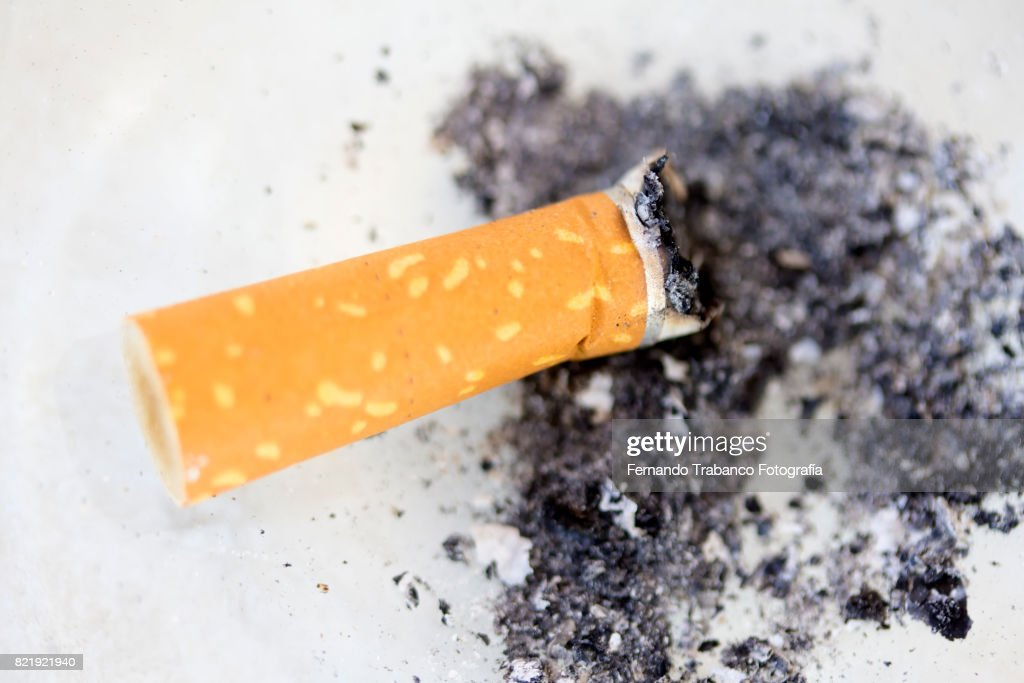 Cigarette and ash in an ashtray : Stock Photo