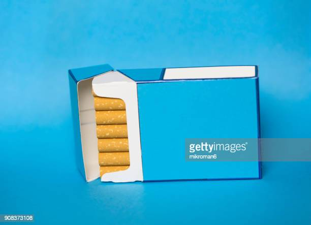 cigarette box and cigarettes on blue background - cigarette packet stock pictures, royalty-free photos & images