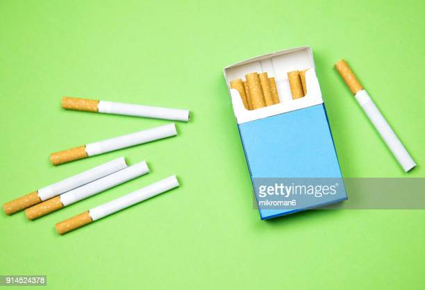 cigarette box and cigarettes on green background - cigarette packet stock pictures, royalty-free photos & images
