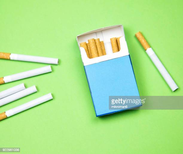 cigarette box and cigarettes on green background - cigarette stock pictures, royalty-free photos & images