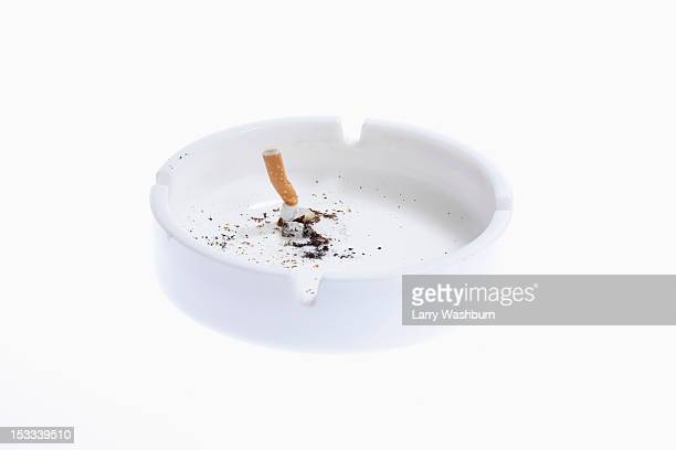 A cigarette butt put out in a white ashtray
