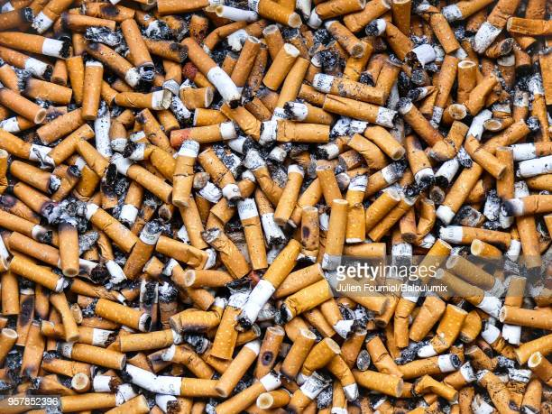 cigarette butts in a public ashtray. - cigarette stock pictures, royalty-free photos & images