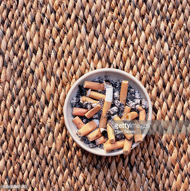 Cigarette butts in ashtray on table, close-up, overhead view
