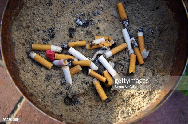 cigarette butts stubbed out in a metal bucket of sand - gum disease stock photos and pictures